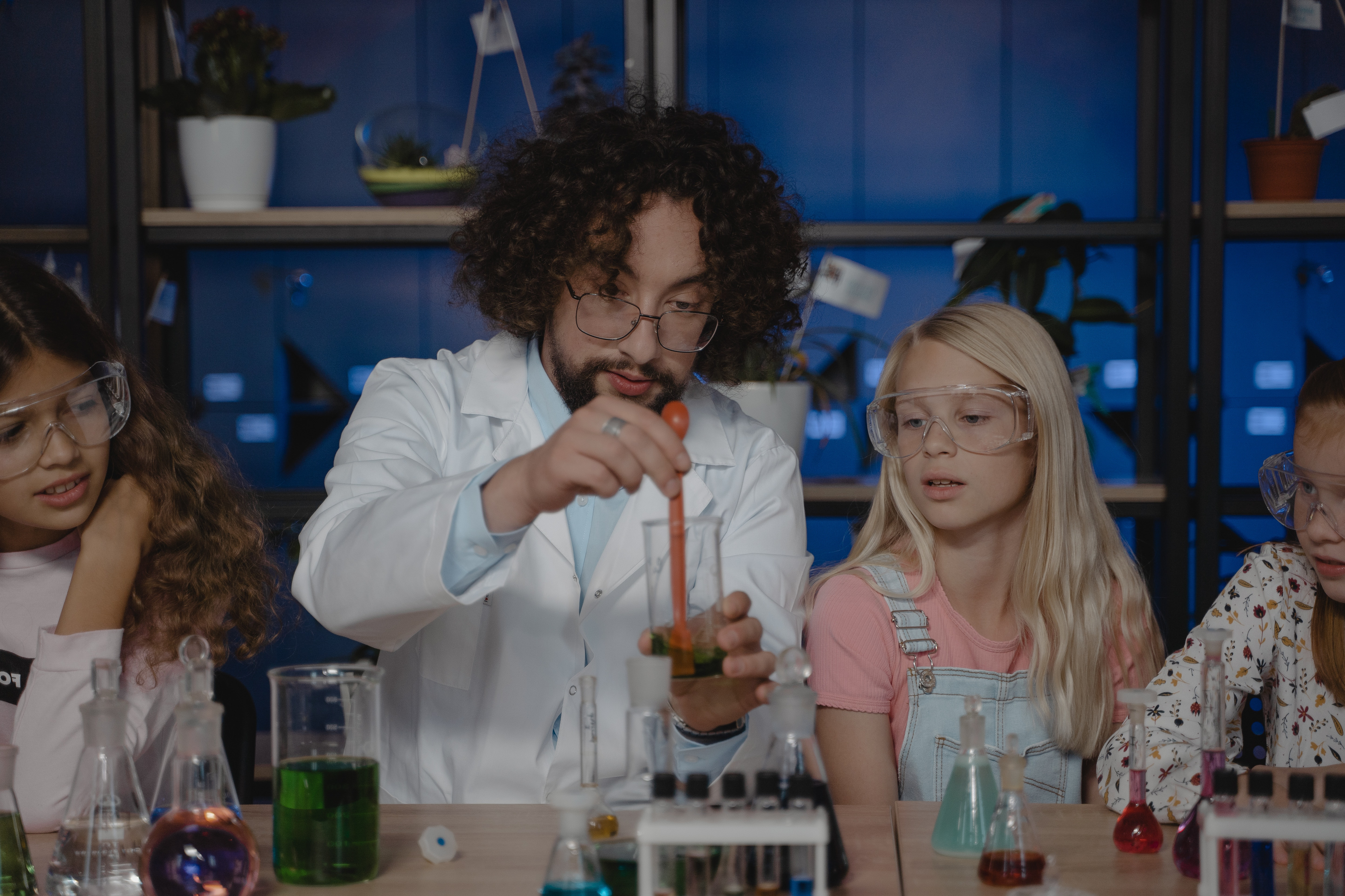 young students participate in a science experiment guided by a male teacher