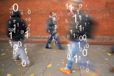 The binary code is superimposed over figures walking along a sidewalk