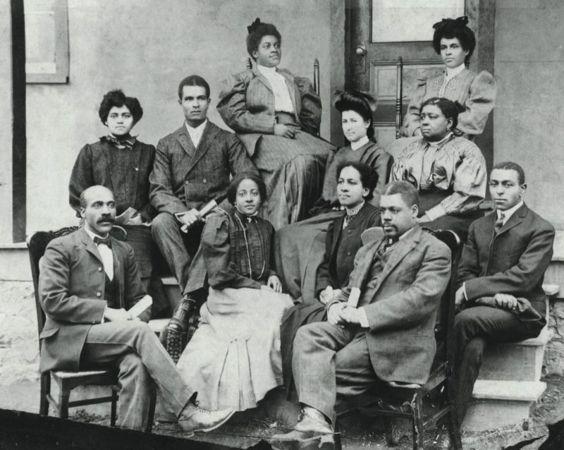 Principals Charles L. Marshall (front row on the left) and Edgar A. Long (front row, second from right) gather with teachers in front of a Christiansburg Institute classroom building.