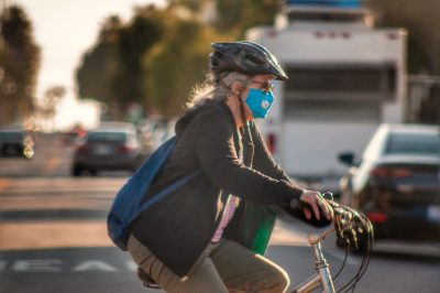 Photo of a woman biking across a street while wearing a mask amid the COVID-19 pandemic.