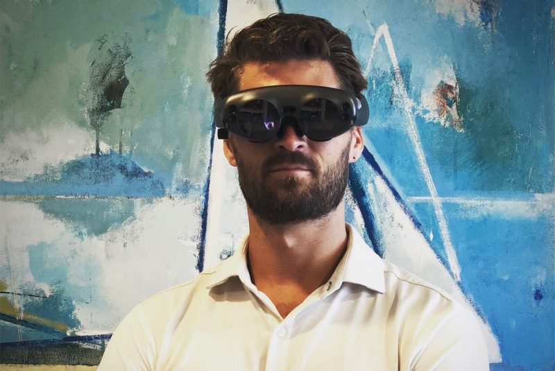 David Gull stands in front of artwork wearing a virtual reality headset