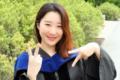 "Eunkyung ""Lucy"" Shin, wearing her graduation gown, uses her fingers to spell out ""VT"""