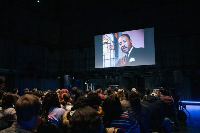 Attendees of the 2019 Rev. Dr. Martin Luther King Jr. Arts and Oration Competition watch footage during the event.