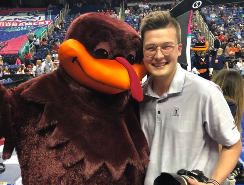 Liam Sment huddles with the Hokie Bird during an ACC Women's basketball game in March 2020, just prior to the placement of COVID-19 pandemic restrictions. Photo courtesy of Liam Sment.