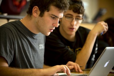 Two male students gaze at a laptop screen