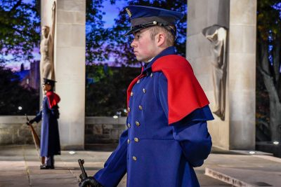 Two cadets in blue dress uniforms and capes stand guard at the Pylons.