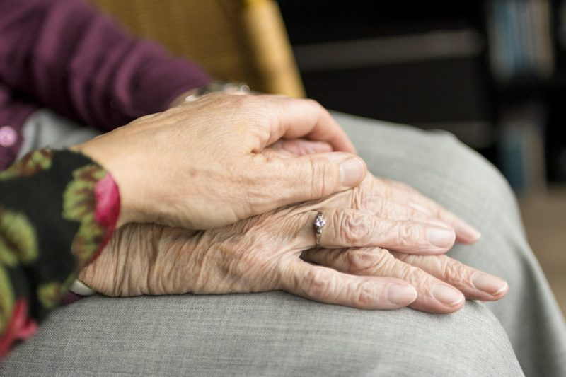 A woman's hand rests upon an older woman's hands