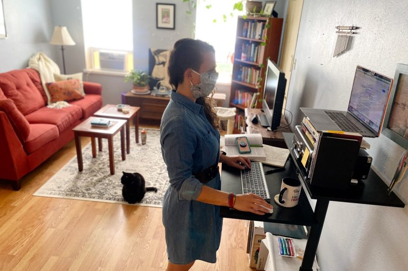 Whitney Hayes stands at a computer workstation in her home. Her cat joins her in the room.