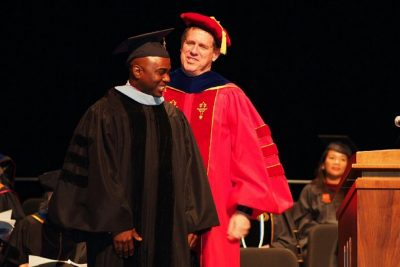 "William ""Bill"" Glenn hoods a graduate student during Commencement."