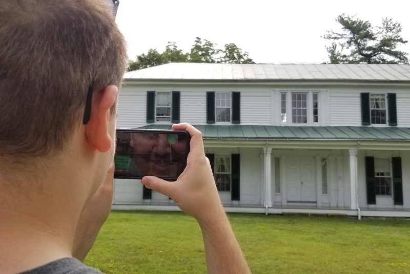 A student working with the VT 150: Visualizing Virginia Tech History project in 2019 views Virginia Tech's oldest building, Solitude, through a smartphone.