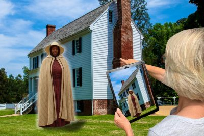 A woman looks at a digital tablet and sees a Civil War era woman standing in front of a historic house.