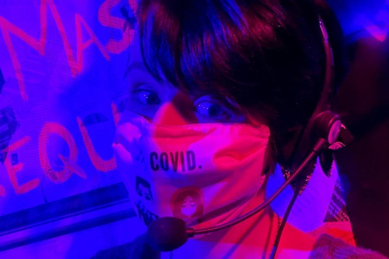 Casey Duke wears a mask. She is lit with purple and fuchsia lights.