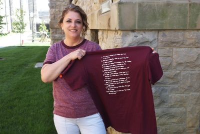 Tammy Henderson holds up a maroon t-shirt with white lettering.