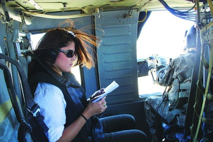 As a foreign correspondent for CNN, Atia Abawi often covered war zones. Here she reviews security briefing materials while traveling to Kunar Province in northeastern Afghanistan on a military helicopter. traveling to Kunar Province in northeastern Afghanistan on a military helicopter.
