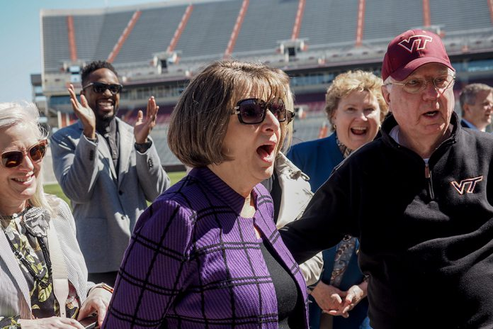 Rosemary Goss (center) and her husband, Bob, look astonished as they realize that the gateway the Virginia Tech football team uses to enter Lane Stadium had been named in her honor. André Davis, a property management alumnus and retired National Football League wide receiver and kick returner, applauds in the background, while advisory board member Alice Fletcher (left) watches and a beaming Julia Beamish (standing behind Bob Goss), head of the Department of Apparel, Housing, and Resource Management, delights in her colleague's response.