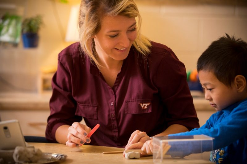 Emily Phillips works with a young boy  on a craft activity.