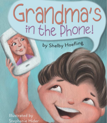 Book cover of Grandma's in the Phone features a child holding a phone with their grandmother's face on it.