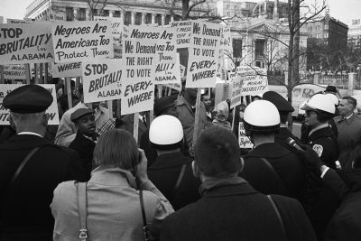 "African American demonstrators outside the White House March 12, 1965 with signs reading, ""We demand the right to vote, everywhere"" and protesting police brutality against civil rights demonstrators in Selma, Alabama."