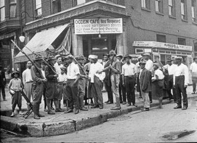 A group of citizens and armed members of the National Guard stand in front of the Ogden Cafe during the race riots in Chicago, Illinois, in 1919.
