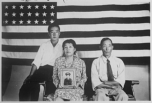 The Hirano family, George (left), Hisa (center) and Yasbei with picture of a United States serviceman at the Colorado River Relocation Center in Poston, Arizona. National Archives.
