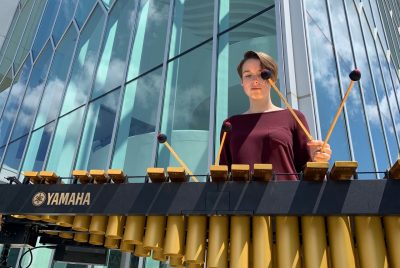 A female college student stands outside, behind a marimba, holding two mallets in each hand.