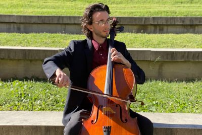 Young man dressed in a dark suit and burgundy shirt sits outdoors and plays the cello