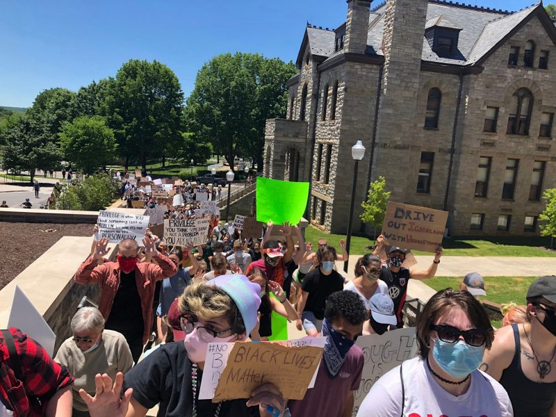 A parade of protestors pass the Virginia Tech College of Liberal Arts and Human Sciences Building in Blacksburg on June 1