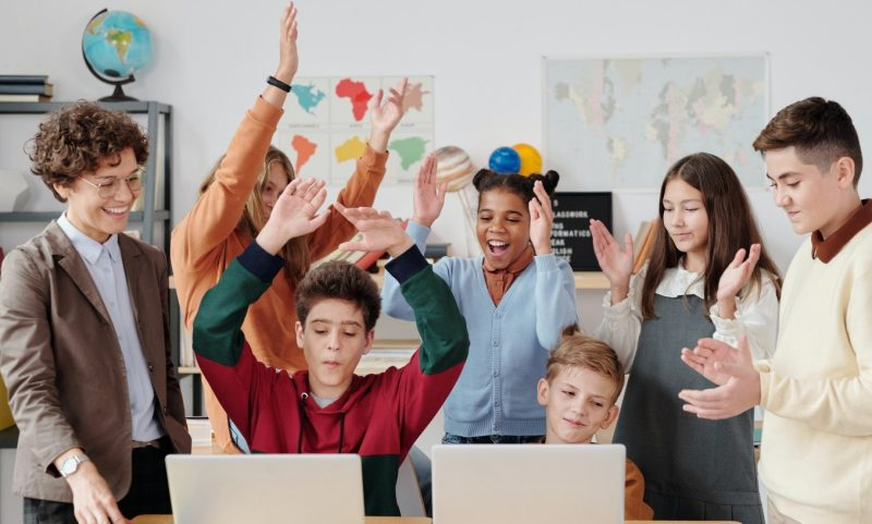 a male teacher demonstrates chemistry to young female students