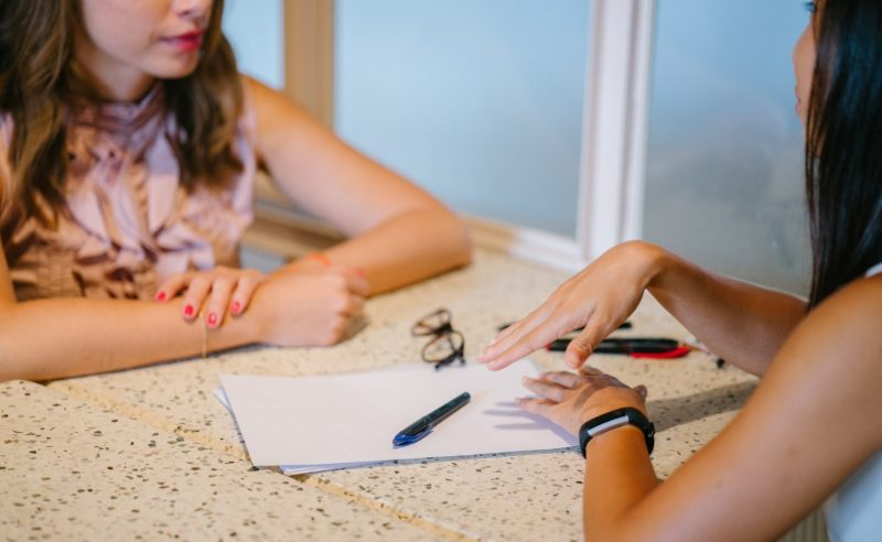a middle aged black woman works with an asian girl in a school setting