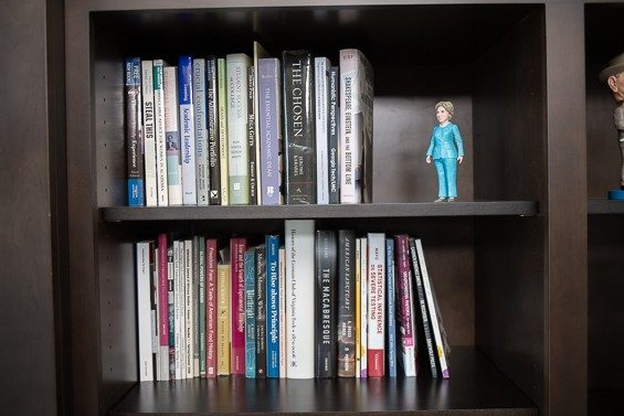 A Hillary Clinton action figure takes a stance near books on higher education; below her are books by the college's faculty members.