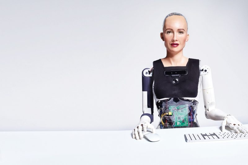 The robot Sophia sits at a keyboard