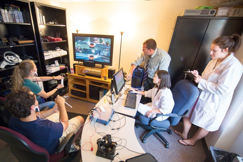 James Ivory (center) and his communication students conduct research into the effects of video games on the people playing them.