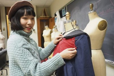 Yiran Zhao makes adjustments to one of her designs for the fashion show.