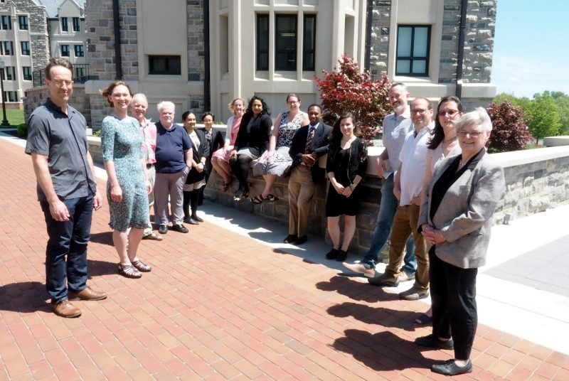 Members of the Department of Religion and Culture gather. Matthew Gabriele, the current chair, is fourth from the right; Brian Britt, former chair, is on the far left.