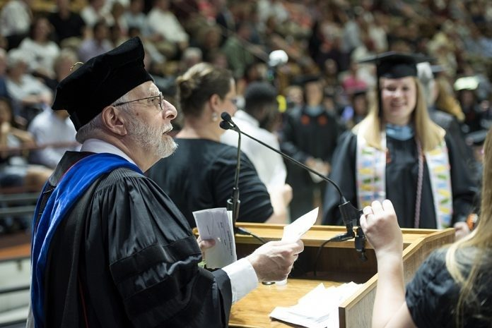Joe Merola reads the names of graduates during the Graduate School Commencement Ceremony in Cassell Coliseum. The chemistry professor has been reading graduate names at commencement for 15 years.