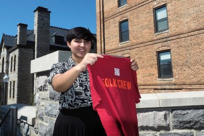 Melissa Velez Nazario holds her t-shirt from the Smithsonian Folklife Festival, where she completed an internship for her Humanities for Public Service major.