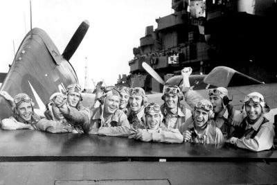 U.S. pilots, pleased over a victory in the Marshall Islands during World War II, grin across the tail of an F6F Hellcat on board the USS Lexington. Courtesy of the National Archives