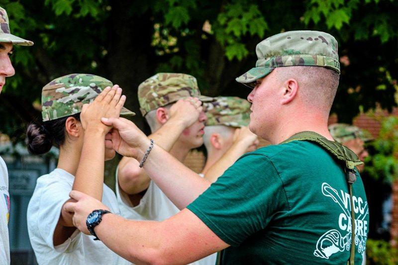 Cadet Stanley Dobis helps a new cadet learn to salute.