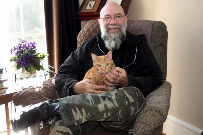 Jeff Mann sits in his writing space with his orange tabby cat, Rory, on his lap.