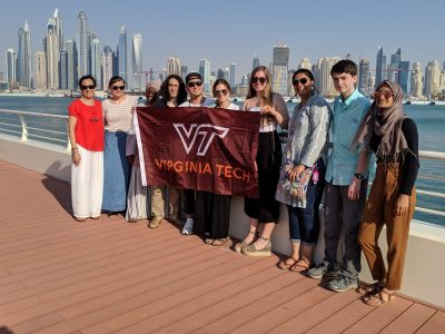 A group of students took a moment to express their Hokie pride in Dubai, holding a Virginia Tech banner with the city's tall buildings in the background.