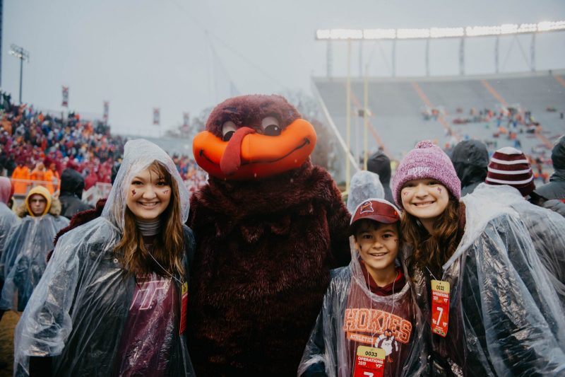 With rain pouring at Lane Stadium, the HokieBird poses for a photo with Sammie Dailly and her younger siblings, who are wearing clear ponchos over Hokie gear.