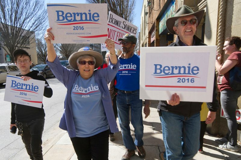 Supporters of Bernie Sanders' 2016 presidential campaign march through the streets of downtown Asheville, North Carolina, carrying signs.
