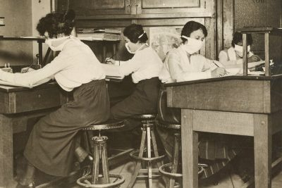 Clerks in masks collect and classify statistics during the 1918 influenza pandemic. Courtesy of the National Archives.