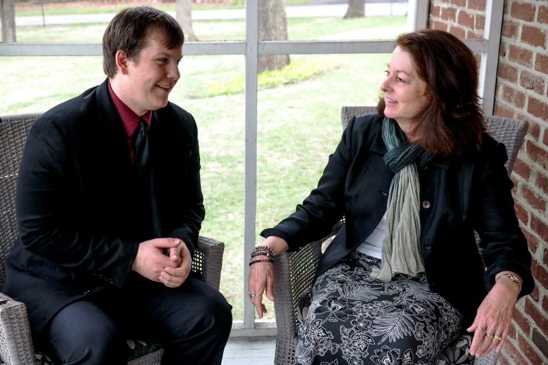 Chris Grogg and Pamela Teaster sit, chatting on a porch
