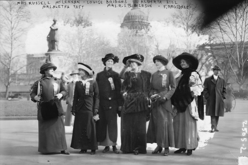A band of suffragists — including Mrs. Russell McLennan, Aletha Taft, Louise Bridges, Mrs. Richard Coke Burleson, Alberta Hill, and F. Ragsdale — gather in front of the Capitol Building in Washington, D.C., on March 3, 1913. A hand-scrawled notation at the top of the photo captures the irony that two of the women were identified by their husband's names. Photo courtesy of the Library of Congress.
