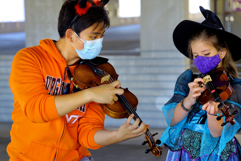 James Kim, a first-year music education student, holds a violin and helps a student play a violin. The young student wore a witch hat and a face covering. Kim wore a Virginia Tech sweatshirt and a face mask. The two both donned Halloween costumes for the String Project gathering in the Perry Street Parking Garage in Blacksburg. The Virginia Tech String Project is a community-outreach program, offering small group and individual instruction on a variety of string instruments. Instruction is provided by graduate and undergraduate teachers, under the supervision of Music faculty