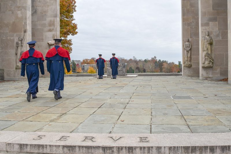 Two cadets in blue dress uniforms march forward to relieve two other cadets standing guard at the Pylons.