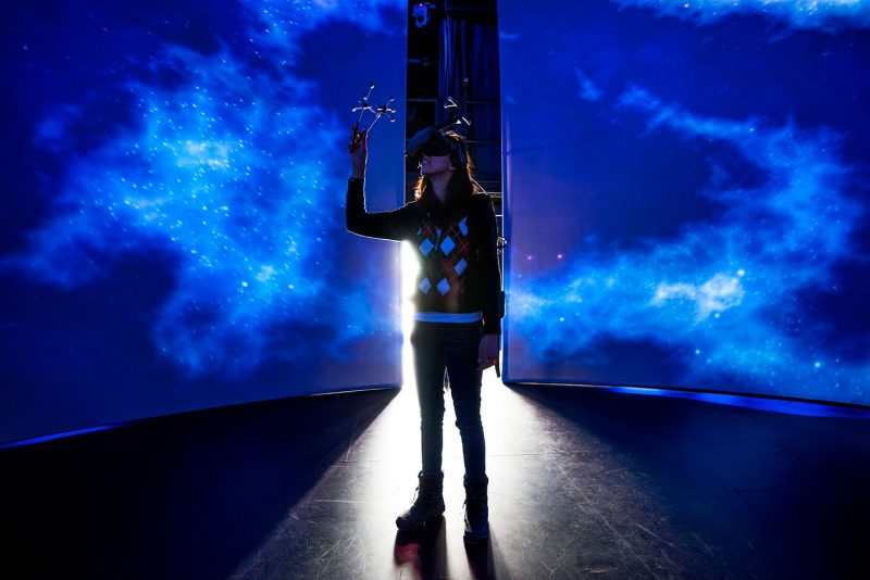 A woman stands in front of a blue background with a headset on her head