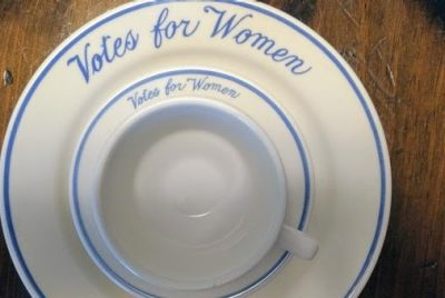 A white cup and saucer, sitting on a white plate, with the words 'Votes for Women' written on it
